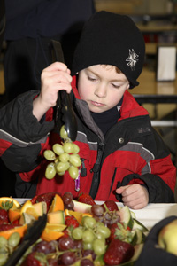 Boy adding grapes to his school meals tray